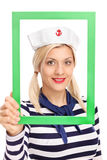 Young female sailor holding a green picture frame royalty free stock photos