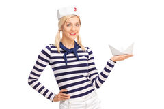 Young female sailor holding a small paper boat. And looking at the camera isolated on white background royalty free stock images