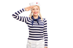 Young female sailor saluting towards the camera. Young blond woman in a sailor outfit saluting towards the camera and smiling isolated on white background Royalty Free Stock Photos