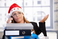 Young female in santa hat troubled in office Royalty Free Stock Photo