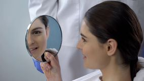 Young female satisfied with rhinoplasty result, smiling face reflected in mirror. Stock photo royalty free stock photo