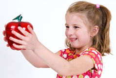 Female school child holding a clear plastic apple. A young female school child holding a clear plastic apple Royalty Free Stock Images