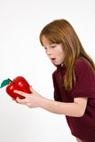 Female school child holding a clear plastic apple. A young female school child in a uniform polo shirt, holding a clear plastic apple Stock Photography