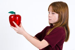 Female school child holding a clear plastic apple. A young female school child in a uniform polo shirt, holding a clear plastic apple Royalty Free Stock Photo