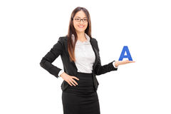 Young female school teacher holding the letter A Royalty Free Stock Photo
