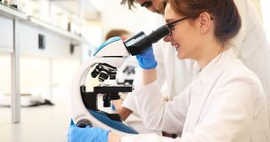 Young scientist looking through microscope in laboratory stock photography