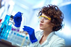 Young female scientist in protective glasses and gloves Royalty Free Stock Image