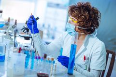 Young female scientist in protective glasses and gloves Stock Images