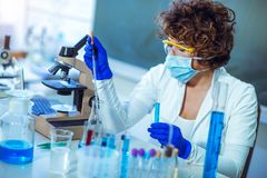 Young female scientist in protective glasses and gloves Stock Image