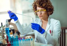 Young female scientist in protective glasses and gloves. Preparing a liquid substance for test tube with a long glass pipette in the scientific chemical Stock Photo