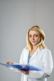 Young female scientist, tech or medical student, text space. Portrait of a young energetic female scientist, tech or medical student with notes in blue folder on Stock Image
