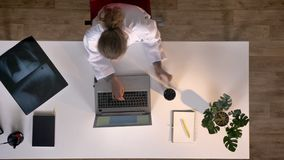 Young female scientist in white coat typing on laptop and drinking coffee, topshot, medical concept.  stock video