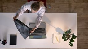 Young female scientist in white coat typing on laptop and looking at x-ray scan, topshot, medical concept.  stock footage