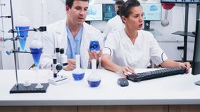 Young female scientist in white coat working with her assistant in a modern research laboratory. Assistant holding a recipient with smoking blue liquid stock footage