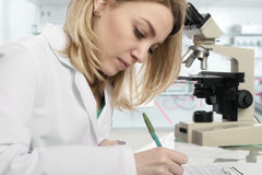 Young female scientist writing in modern laboratory. Young female scientist or tech writes report in modern laboratory, This image is toned Stock Image