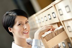 Young female searches something in card catalog Stock Photo
