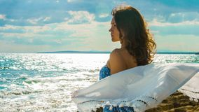 Young female on seashore, wind waving scarf in her hands. Woman enjoying freedom. Stock footage stock footage