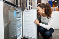 Young female selecting domestic refrigerator Royalty Free Stock Photos