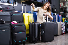 Young female selecting travel suitcase. In haberdashery store Stock Images