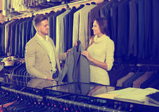 Young female seller demonstrating men's shirts to customer Stock Photography