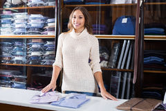 Young female seller demonstrating shirts in men's cloths store Stock Image