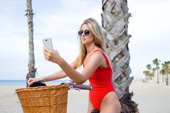 Young female in sexy bikini photographing herself on mobile phone Royalty Free Stock Photography