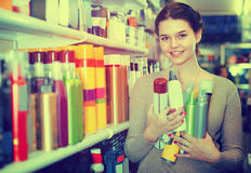Young female shop assistant is demonstrating hair care product Royalty Free Stock Photography