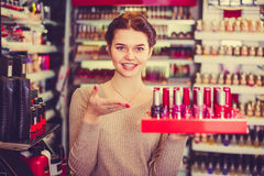 Young female shop assistant is demonstrating nail lacquer Stock Photography