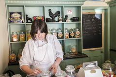 Young female shop assistant serving  candy. Telford, England.- July 9th 2014 : Young female shop assistant serving  candy sweets  in Victorian Confectioner Old Royalty Free Stock Photos