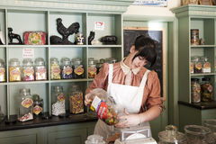 Young female shop assistant serving  candy. Telford, England.- July 9th 2014 : Young female shop assistant serving  candy sweets  in Victorian Confectioner Old Stock Photo
