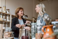 A female shop assistant serving a senior customer in a zero-waste shop. royalty free stock images