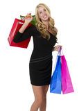 Young Female Shopper. Young blonde female shopper in black dress carrying colorful shopping bags stock photo