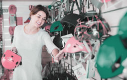 Young female shopper examining helmets in sports equipment store Stock Photography