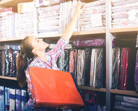 Young female shopper searching for bed linen Royalty Free Stock Photo