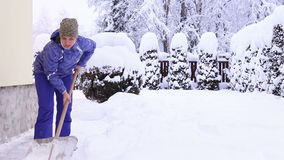 Young female shoveling near own house after snowfall stock footage