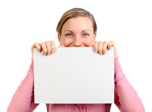 Young female showing a white card. Young blonde female holding a white card with both hands above her mouth (isolated on white Royalty Free Stock Photography