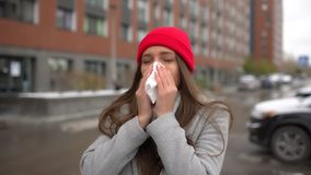 Young female sick woman, girl blowing nose to paper napkin and sneezing at street outside, healthcare, flu, people stock video footage