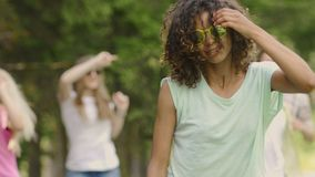 Young female singer dancing in music clip, backup dancers partying on background