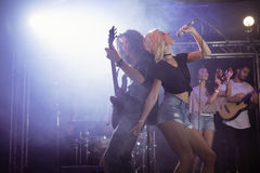 Young female singer with male guitarist performing at nightclub. Young female singer with male guitarist performing together at nightclub during music festival Royalty Free Stock Photos