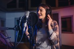 Singer recording album in the studio. Young female singer recording album in the professional studio. Woman singing a song in music recording studio Royalty Free Stock Image