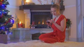 Young girl in red dress sit on floor near Christmas tree and using her phone stock video