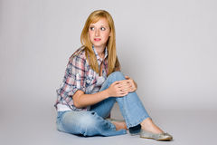 Young female sits on the floor, grey background Stock Photo