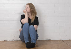 Young female sitting against a white brick wall Royalty Free Stock Photos