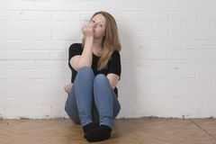 Young female sitting against a white brick wall Stock Photos