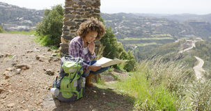 Young female sitting with backpack and map Royalty Free Stock Image