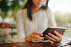 Young female sitting at cafe table with digital tablet Stock Images