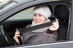 Woman sitting in car and holding seat belt Stock Image
