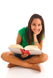 Young female sitting cross legged reading a book Royalty Free Stock Photography