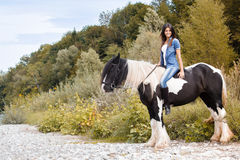 Young female sitting on her horse and looking at c. Beautiful young female sitting on her horse and looking at camera Stock Image