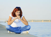 Young female sitting near river in summer day Stock Photos